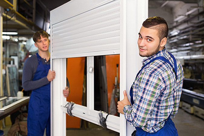 Two young careful workmen inspecting windows with shutter at workshop